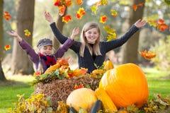 Zwei Mädchen, die witzh Herbstblätter spielen Stockfotos