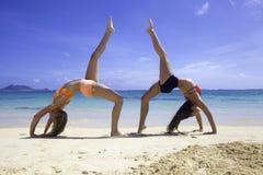 Zwei Mädchen, die Yoga auf dem Strand tun Stockfotos