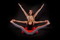 Zwei Mädchen, die Yoga tun Stockfotografie