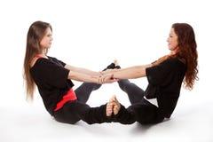 Zwei Mädchen, die Yoga tun Stockfotos