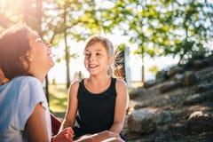 Zwei Mädchen, die zusammen auf einem Spielplatz im Sommer lachen Stockbilder