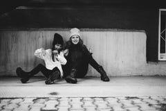Zwei Mädchen, die zusammen in der Straße spielen Stockfotos