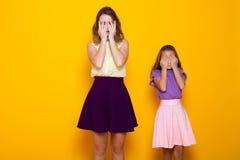 Zwei Mädchen drehen ein blindes Auge Stockfotografie