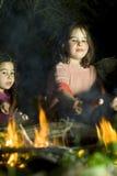 Zwei Mädchen an einem Feuer Lizenzfreie Stockfotos