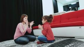 Zwei Mädchen, eins von ihnen mit Down-Syndrom, zu Hause sitzend auf dem Teppich, Spiel und haben Spaß stock video