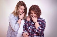 Zwei Mädchen entsetztes Anstarren entlang des Smartphone Stockfotografie