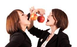 Zwei Mädchen gebissene Äpfel Stockfotos