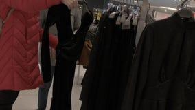 Zwei Mädchen gehen um die Butike im Einkaufszentrum und wählen ein Abendkleid Langsame Bewegung stock video