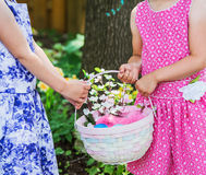 Zwei Mädchen-Hände, die einen Ostern-Korb halten Lizenzfreies Stockfoto