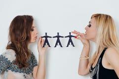 Zwei Mädchen halten Papierleute auf einem Weiß lizenzfreies stockbild