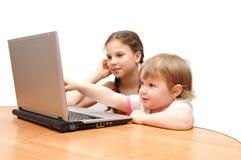 Zwei Mädchen hinter dem Laptop Stockfoto