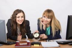 Zwei Mädchen im Büro mit der Uhr erwarten glücklich das Ende des Arbeitstages Lizenzfreie Stockfotografie