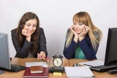 Zwei Mädchen im Büro mit einem Lächeln, auf das Ende des Arbeitstages wartend Lizenzfreies Stockfoto