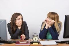 Zwei Mädchen im Büro, welches auf das Ende von Arbeitsstunden auf der Uhr wartet und einander betrachtet Stockfoto