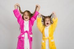Zwei Mädchen im Bademantel-Grimassenhaar lizenzfreie stockfotos