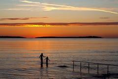 Zwei Mädchen im Meer mit Sonnenuntergang Stockbild