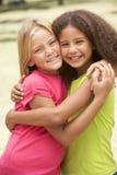 Zwei Mädchen im Park, der Umarmung sich gibt Stockfotos