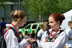 Zwei Mädchen im traditionellen polnischen Kostümplaudern Lizenzfreie Stockbilder