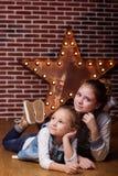 Zwei Mädchen liegen zu Hause in der vorderen Backsteinmauer Stockbild