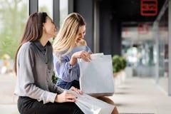 Zwei Mädchen mit dem Einkaufen, das auf einer Bank im Mall sitzt lizenzfreie stockbilder