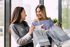 Zwei Mädchen mit dem Einkaufen, das auf einer Bank im Mall sitzt stockfotografie
