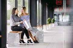 Zwei Mädchen mit dem Einkaufen, das auf einer Bank im Mall sitzt Lizenzfreie Stockfotos