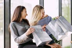 Zwei Mädchen mit dem Einkaufen, das auf einer Bank im Mall sitzt stockbild