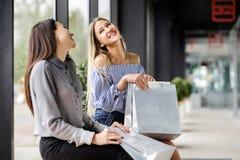 Zwei Mädchen mit dem Einkaufen, das auf einer Bank im Mall sitzt Lizenzfreies Stockbild