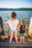 Zwei Mädchen mit dem Hund, der auf Dock steht Stockfotos