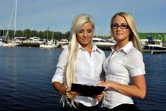 Zwei Mädchen mit den Dokumenten, die auf dem Pier stehen Stockfoto