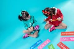Zwei Mädchen mit Down-Syndrom, die an Wörtern auf Nummernschildern interessiert werden stockbilder