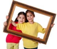 Zwei Mädchen mit einem Bilderrahmen Lizenzfreies Stockfoto