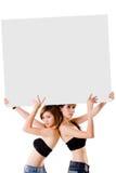 Zwei Mädchen mit einem großen Zeichen Stockbild