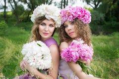 Zwei Mädchen mit rosafarbenem Pfingstrosenkranz Stockfoto