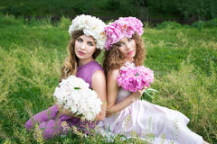 Zwei Mädchen mit rosafarbenem Pfingstrosenkranz Stockfotografie