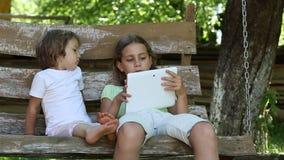 Zwei Mädchen mit Tablet-Computer sitzen auf der Schwingenbank stock video footage