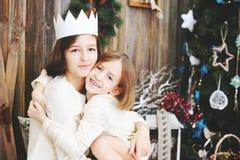 Zwei Mädchen nähern sich Weihnachtsbaum stockfoto