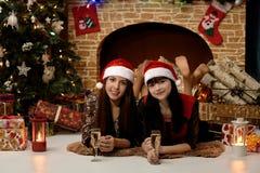 Zwei Mädchen nahe dem Kamin und dem Weihnachtsbaum Lizenzfreies Stockfoto