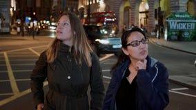 Zwei Mädchen an Piccadilly-Zirkus nachts - London-Besichtigung bis zum Nacht stock footage