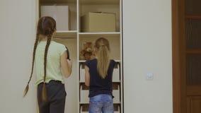 Zwei Mädchen setzten ihre Sachen in einen Schrank nach der Verlegung in einem neuen Haus stock video footage