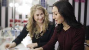Zwei Mädchen sind die Meister der Schönheit angespornt durch Modetrends, indem sie eine Modezeitschrift grasen stock video footage