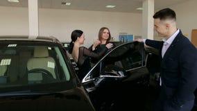 Zwei Mädchen sind glücklich, einen Neuwagen zu kaufen, der Verkäufer gibt ihnen die Schlüssel stock video