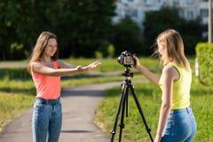 Zwei Mädchen sind Studenten Sommer in der Natur Leiten Sie ein Gespräch Rekord-vlog und Blog Rekordvideolektion für Internet Lizenzfreie Stockbilder