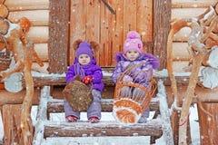 Zwei Mädchen sitzen auf den Schritten im Winter Lizenzfreies Stockfoto