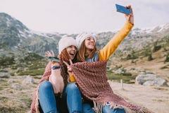 Zwei Mädchen sitzen in der Wiese und machen ein Foto mit ihrem Mobile stockfotos