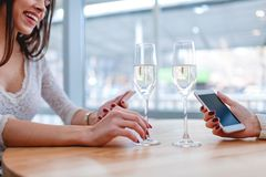 Zwei Mädchen sitzen in einem Café, unter Verwendung der Handys und des trinkenden Champagners stockfotografie