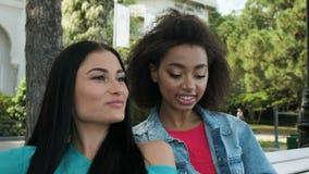 Zwei Mädchen sitzen im Parkchat und lesen eine Zeitschrift stock video