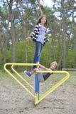 Zwei Mädchen spielen auf dem Spielplatz auf der gelbes Metallanziehungskraft Es ist windig lizenzfreie stockbilder