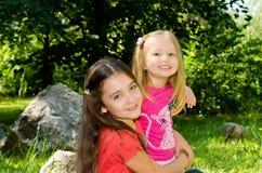 Zwei Mädchen spielen in einem Park auf einem Rasen unter enormen Steinen. Stockfotos