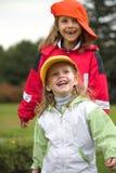 Zwei Mädchen spielen mit Schutzkappe stockbilder